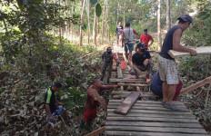 Bersama Warga, Prajurit Satgas Yonif 642 Perbaiki Jembatan yang Rusak Akibat Banjir - JPNN.com