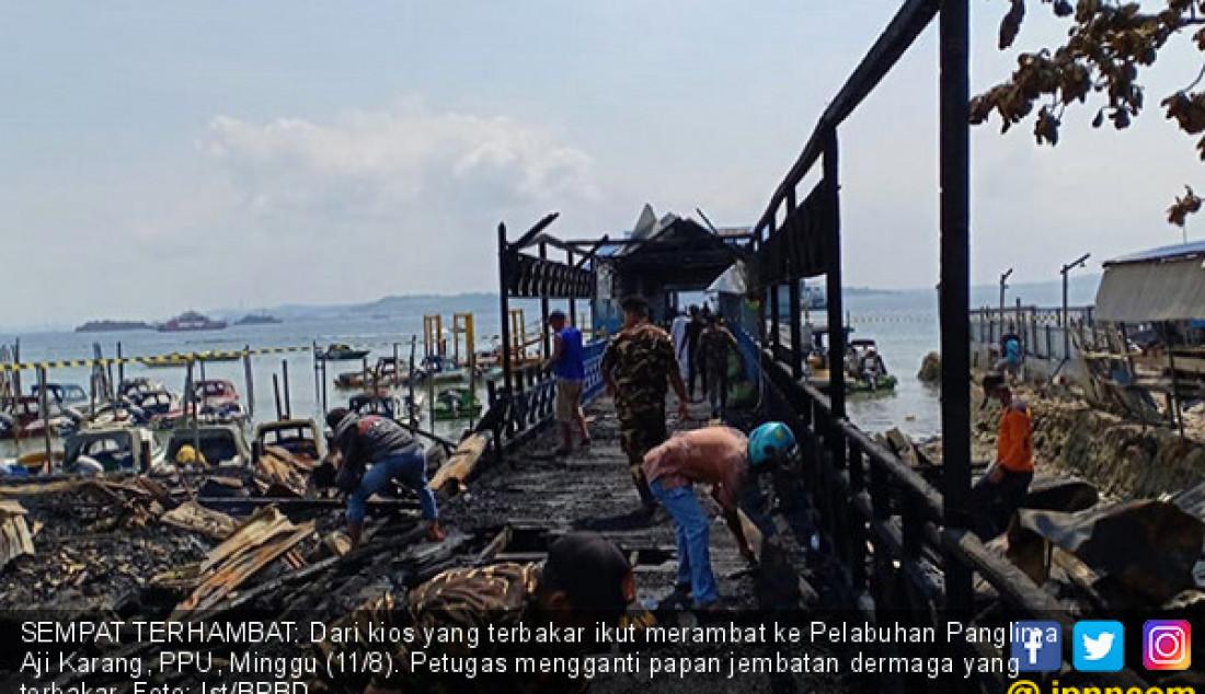 SEMPAT TERHAMBAT: Dari kios yang terbakar ikut merambat ke Pelabuhan Panglima Aji Karang, PPU, Minggu (11/8). Petugas mengganti papan jembatan dermaga yang terbakar. Foto: Ist/BPBD - JPNN.com