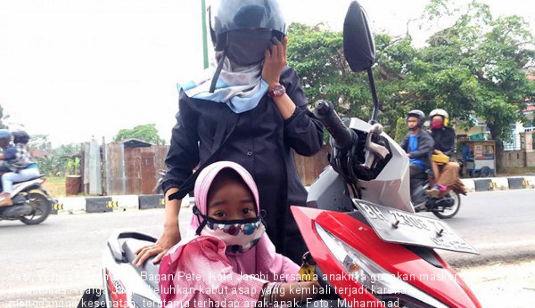 Yesi, Warga Kecamatan Bagan Pete, Kota Jambi bersama anaknya gunakan masker saat beraktifitas. Warga Jambi keluhkan kabut asap yang kembali terjadi karena mengganggu kesehatan, terutama terhadap anak-anak. Foto: Muhammad Hanapi/ANTARA/JPNN.com - JPNN.com