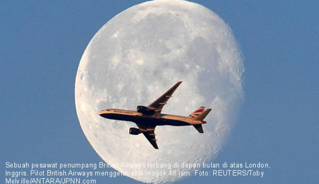 Sebuah pesawat penumpang British Airways terbang di depan bulan di atas London, Inggris. Pilot British Airways menggelar aksi mogok 48 jam. Foto: REUTERS/Toby Melville/ANTARA/JPNN.com - JPNN.com