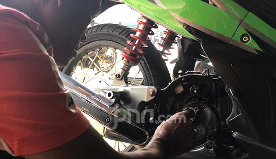 Mekanik melakukan perbaikan sekaligus perawatan sepeda motor pelanggan di bengkel miliknya, kota Ciledug, Tangerang, Selasa (10/9). Foto: Anam - JPNN.com