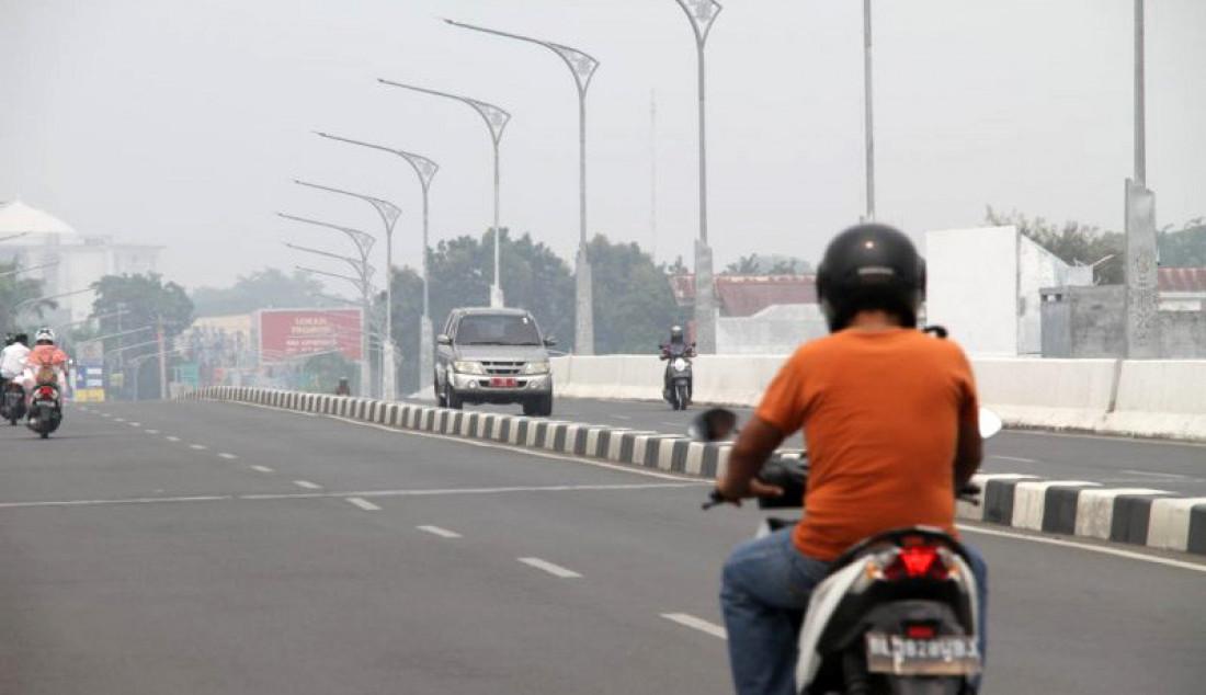 Seorang pengendara motor melintasi kawasan jalan layang simpang Surayaba di Banda Aceh, Selasa (24/9). Perlahan kabut asap yang meliputi kawasan di Aceh mulai berkurang. Foto: Khalis/ANTARA/JPNN.com - JPNN.com