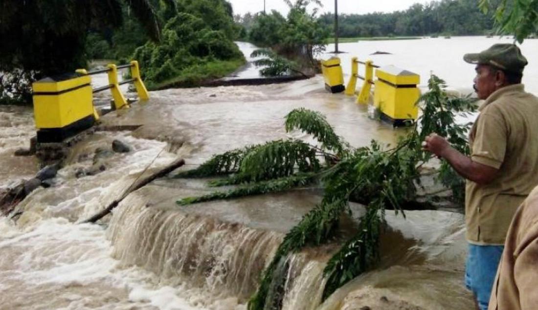 Warga Cacang Randah, Nagari Tiku Utara, Kecamatan Tanjungmutiara, Kabupaten Agam, melihat jalan yang amblas akibat banjir yang terjadi karena hujan membuat air Sungai Batang Tiku meluap, Selasa (22/19). Foto: BPBD/ANTARA/JPNN.com - JPNN.com