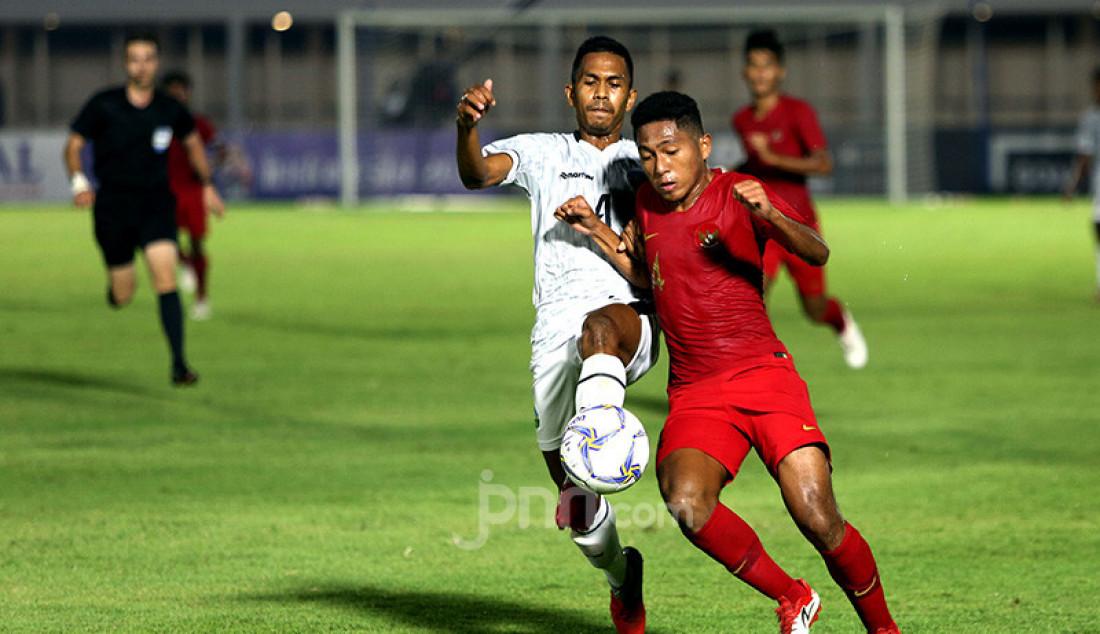 Pemain U-19 Indonesia Muhammad Fajar Fathur berduel dengan pemai U-19 Timor Leste Orcelio Nobelito Moises pada Kualifikasi AFC U-19 Championship 2020 di Stadion Madya, Jakarta, Rabu (6/11). U-19 Indonesia menang atas lawannya dengan skor 3-1. Foto: Ricardo - JPNN.com