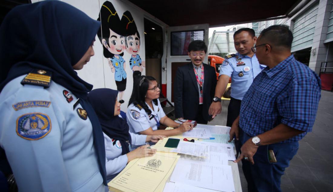 Direktur Smartfren Marco Sumampow (ketiga kanan) dan Kepala Seksi Infokim Kantor Imigrasi Kelas 1 Non TPI Jakarta Pusat Alvian Bayu (kedua kanan) berbincang dengan masyarakat yang sedang mengurus passport di Jakarta. Foto: Ricardo - JPNN.com