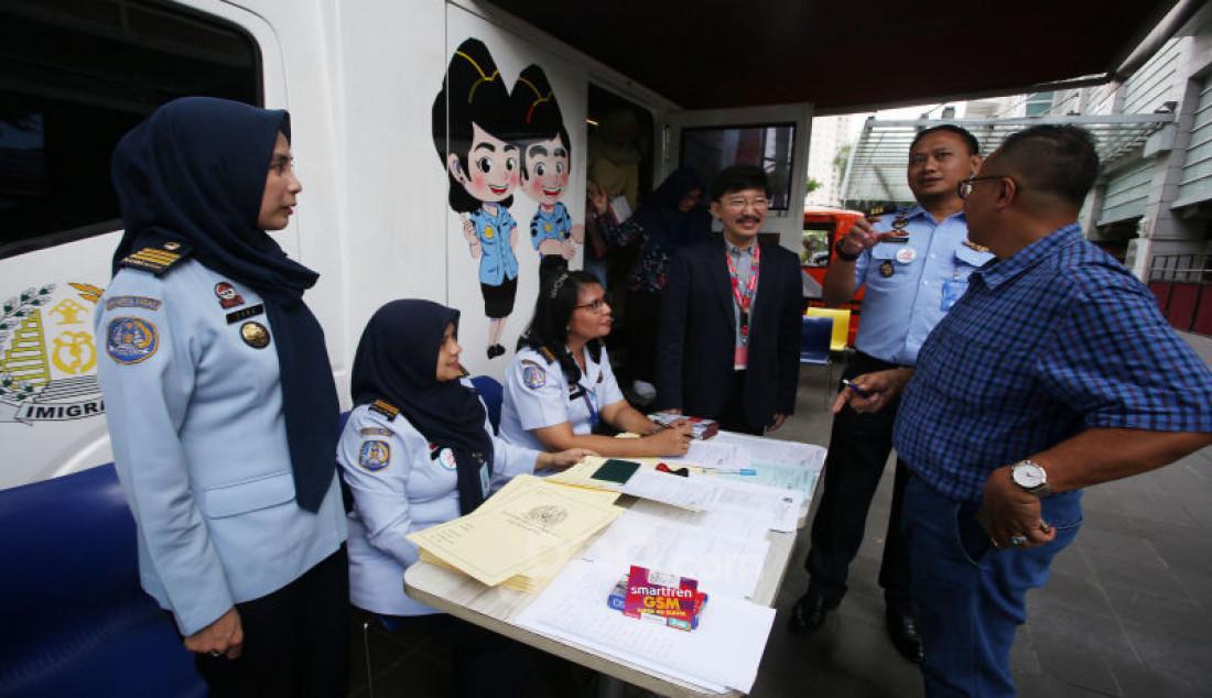 Direktur Smartfren Marco Sumampow (ketiga kanan) dan Kepala Seksi Infokim Kantor Imigrasi Kelas 1 Non TPI Jakarta Pusat Alvian Bayu (kedua kanan) berbincang dengan masyarakat yang sedang mengurus passport di Jakarta, Selasa (19/11). Smartfren bekerja sama dengan kantor imigrasi kelas 1 Jakarta Pusat menyiapkan sarana dan prasarana perangkat telekomunikasi untuk mendukung Pelayanan Paspor Keliling. Foto: Ricardo - JPNN.com