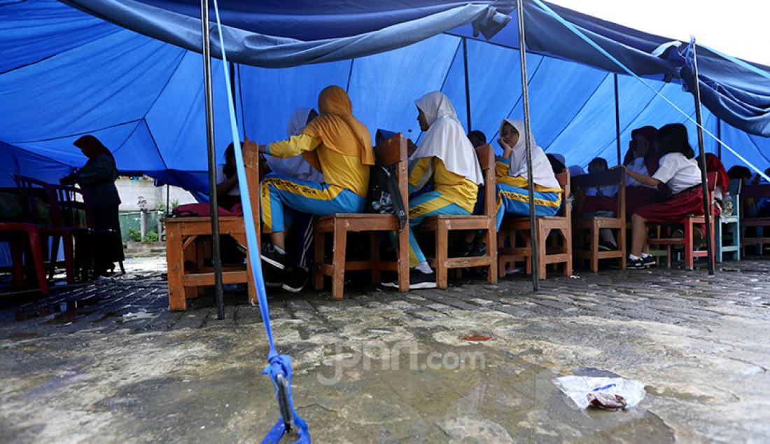 Siswa gabungan kelas 4, 5 dan 6 belajar dalam tenda darurat akibat bangunan atap kelas roboh saat hujan deras di SDN Cirimekar 2, cibinong, Bogor, Selasa (6/1). Selain ditenda darurat mereka juga belajar di lorong kelas. Foto: Ricardo - JPNN.com
