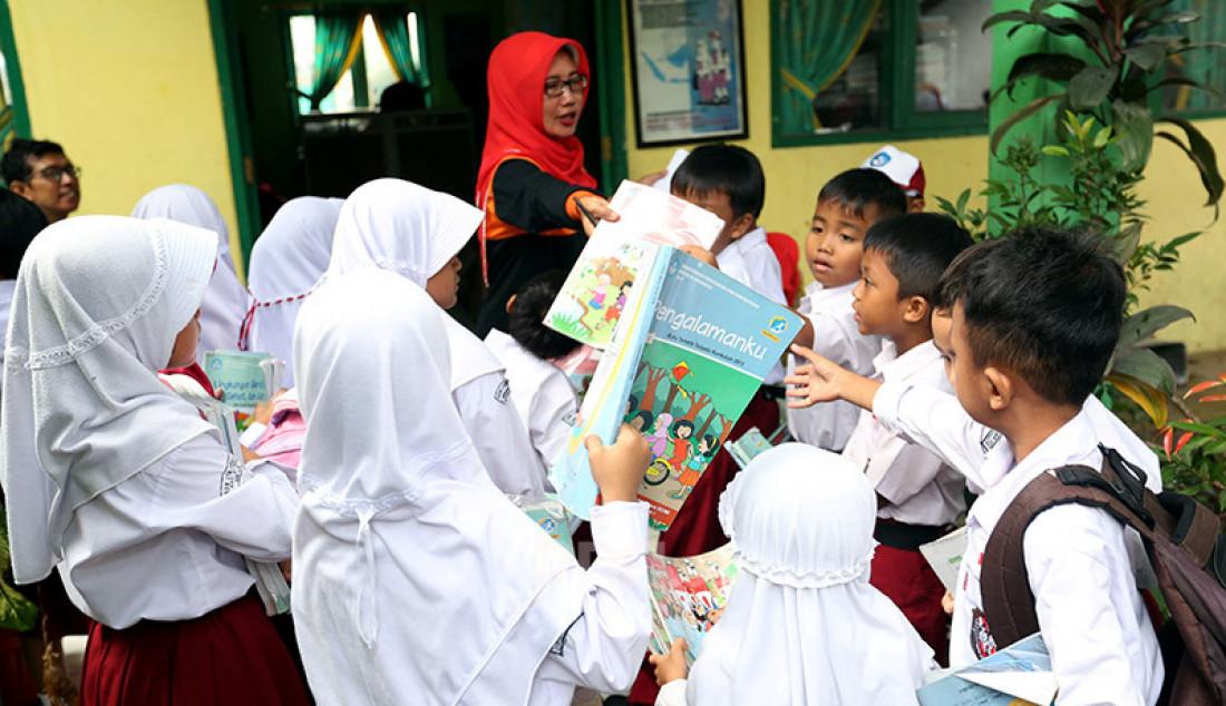 Sejumlah guru membagikan buku bacaan dan peralatan tulis siswa-siswi yang merupakan bantuan dari Mendikbud di SDN Cirimekar 2, Cibinong, Bogor, Selasa (6/1). Foto: Ricardo - JPNN.com
