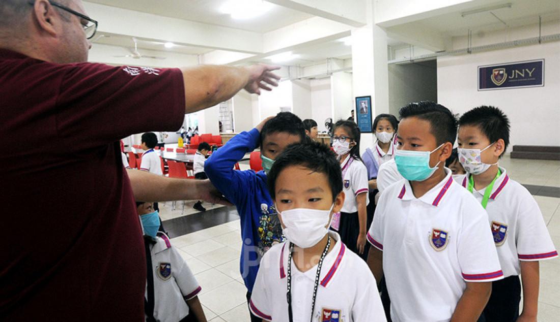 Murid-murid sekolah dasar menjalani pemeriksaan suhu tubuh sebelum memasuki lingkungan sekolah di Jakarta Nanyang School (JNY), Tangerang Selatan, Selasa (3/3). JNY melakukan pengecekan suhu tubuh secara berkala kepada para siswa. Foto: Ricardo - JPNN.com