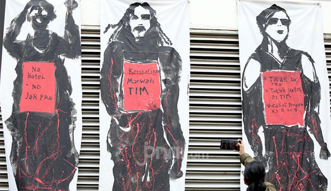 Seorang warga melintas di depan Mural Save TIM di Taman Ismail Marzuki, Jakarta, Selasa (3/3). Foto: Ricardo - JPNN.com