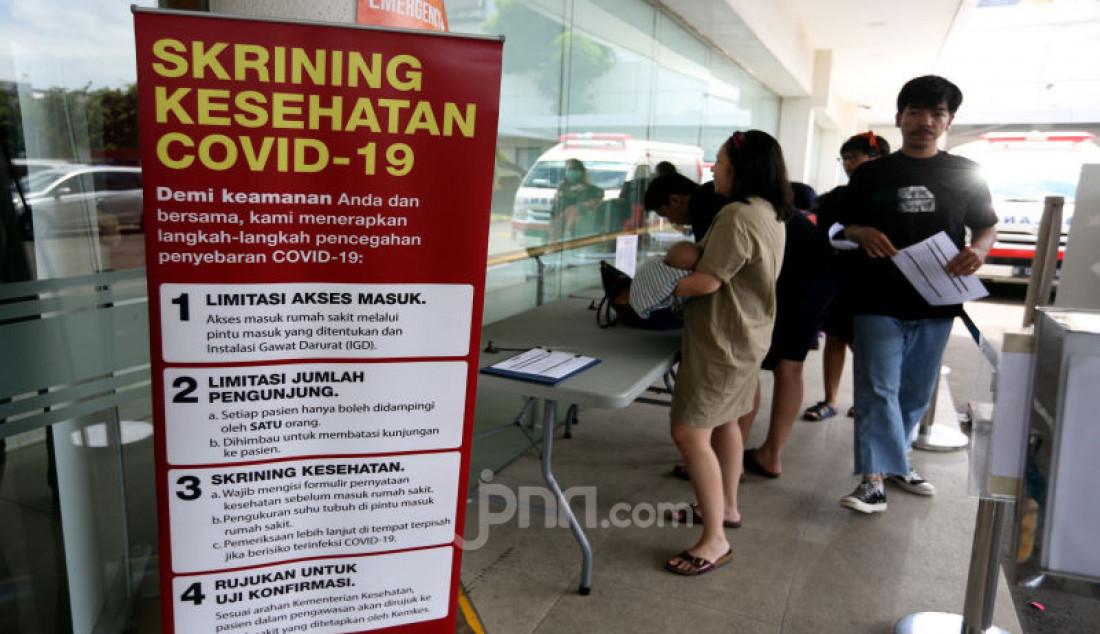 Pengunjung mengisi formulir pernyataan kesehatan sebelum memasuki Rumah Sakit Siloam, Jakarta, Sabtu (7/3). Foto: Ricardo - JPNN.com