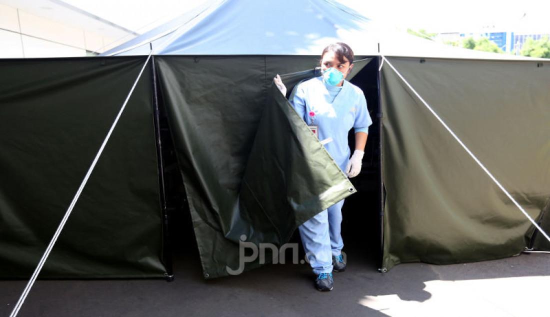 Petugas keluar dari tenda isolasi sementara yang disediakan di Rumah Sakit Siloam, Jakarta, Sabtu (7/3). RS Siloam menyediakan fasilitas tenda isolasi sementara, ruangan dekontaminasi dan pengecekan suhu tubuh guna mengantisipasi penyebaran virus corona COVID-19. Foto: Ricardo - JPNN.com