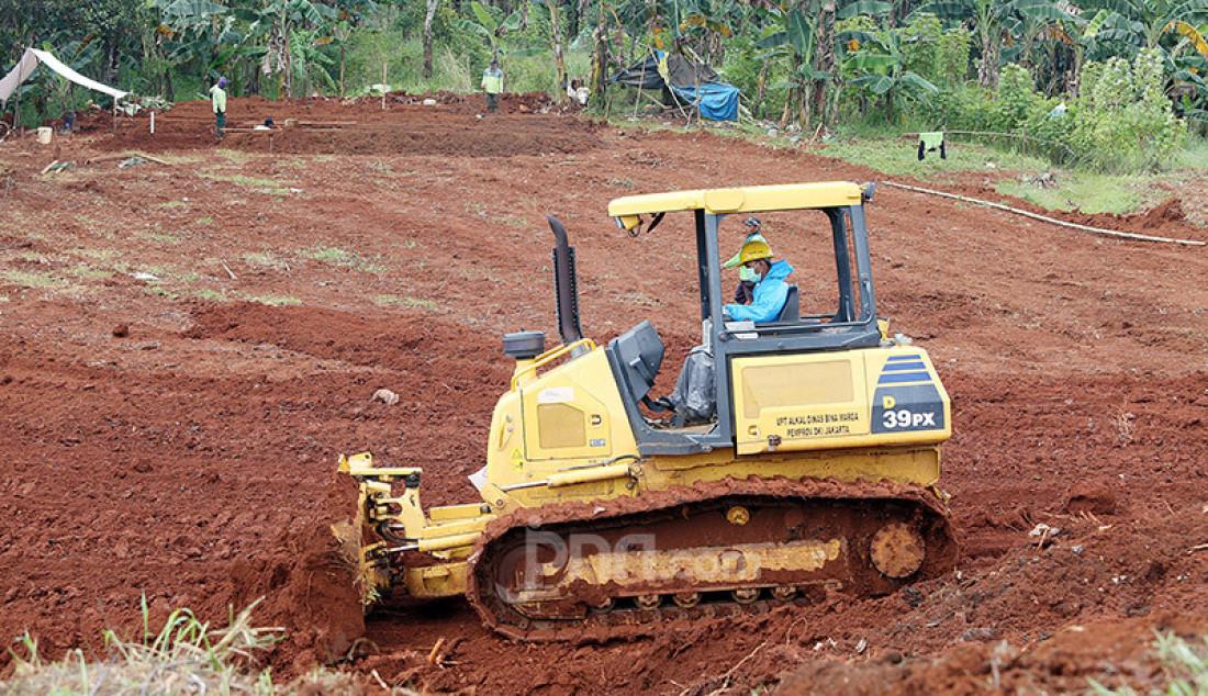 Petugas menguruk tanah untuk melebarkan lahan pemakaman bagi jenazah korban Covid-19 di TPU Pondok Ranggon, Cipayung, Jakarta Timur, Rabu (1/4). Foto: Ricardo - JPNN.com