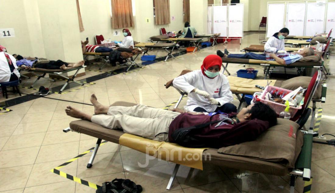 Sejumlah relawan sedang melakukan donor darah sekaligus mengedukasi masyarakat tentang aktivitas donor darah tetap aman di tengah kondisi wabah virus Covid-19 yang berlangsung di kantor PMI DKI Jakarta, Selasa (31/3). Foto: Ricardo - JPNN.com
