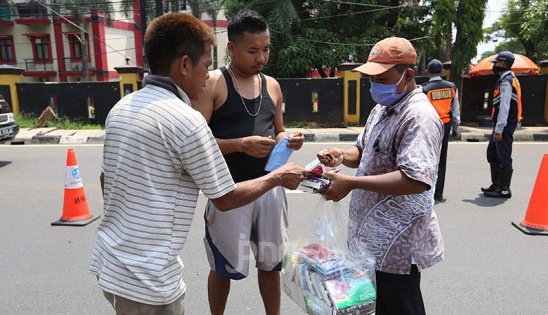 Aparat Polri bersama Dishub memeriksa pengendara roda dua dan empat di Jalan Ciputat Raya, Jakarta, Jumat (10/4). Pemeriksaan bertujuan menghimbau pengendara untuk menggunakan masker selama PSBB. Foto: Ricardo - JPNN.com