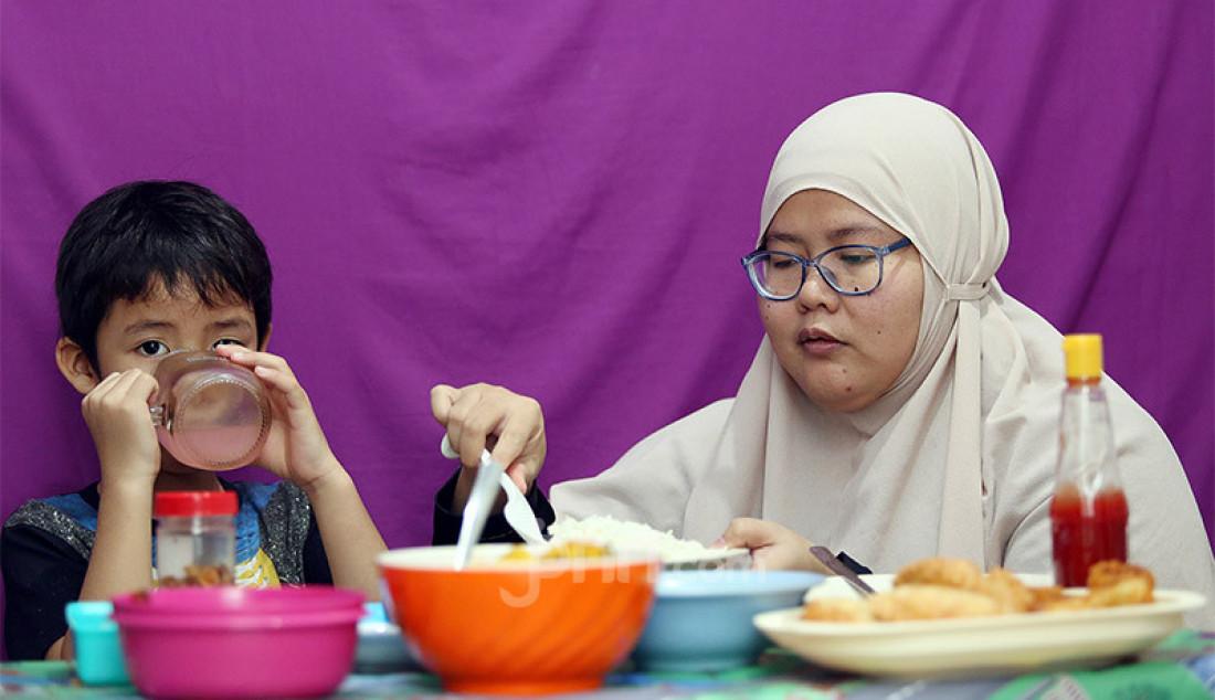 Seorang anak saat berbuka puasa bersama ibunya di bulan suci Ramadhan 1441 H, Kabupaten Bogor, Kamis (7/5). Anak usia 5 tahun atau lebih sudah layak diperkenalkan untuk berpuasa dengan waktu minimal 4-5 jam dalam sehari. Foto: Ricardo - JPNN.com