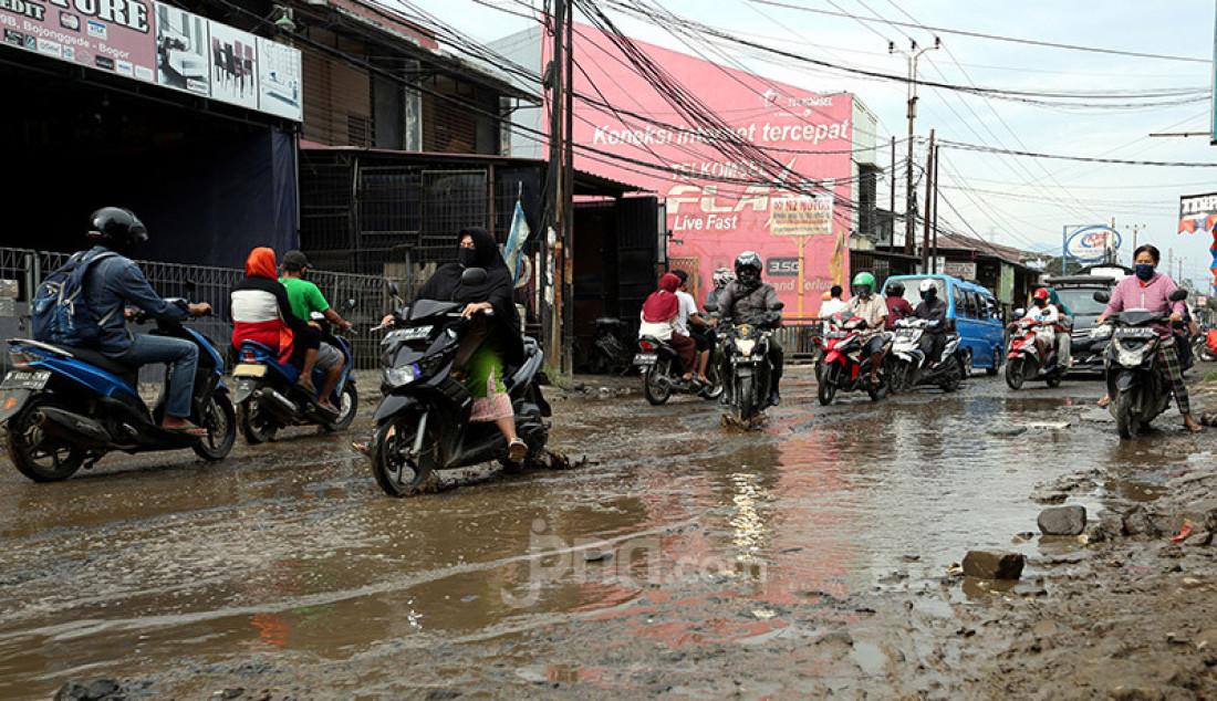 Pengendara roda dua dan emapt melintas jalan berlubang yang tergenang air dan lumpur di Jalan Raya Bojonggede, Bogor Senin (11/5). Jalan rusak tersebut merupakan jalan penghubung antara Citayam dengan Bojonggede. Foto: Ricardo - JPNN.com