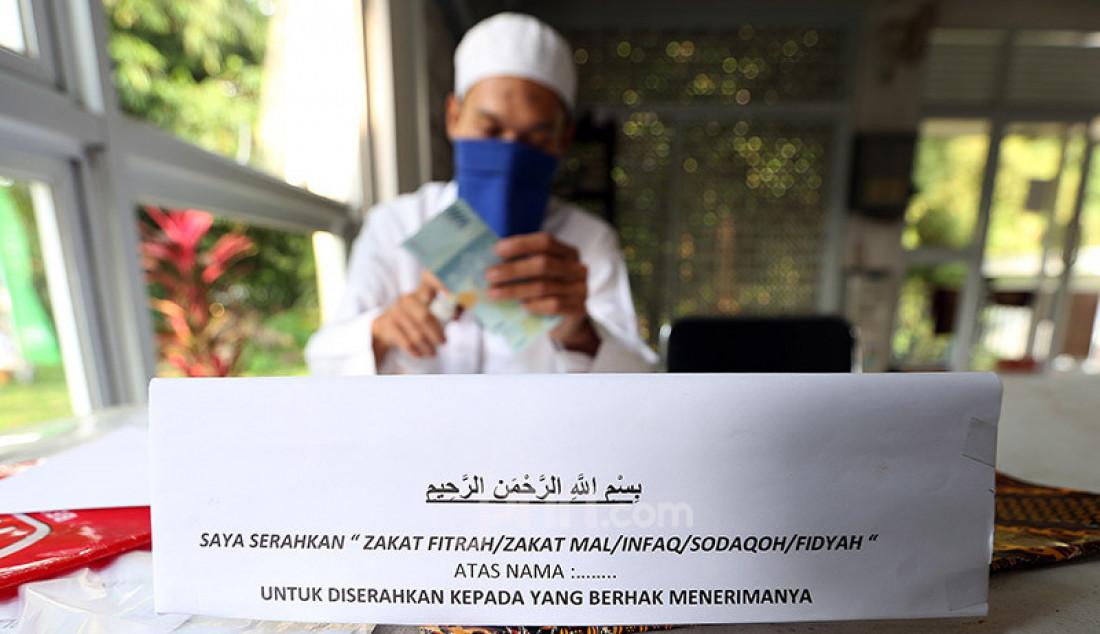 Petugas menerima pembayaran zakat fitrah di Mushola Al Ijabah, Kamis (14/5). Memasuki 10 hari terakhir bulan Ramadhan, warga mulai menyetorkan zakat fitrah di tengah pandemi Covid-19. Foto: Ricardo - JPNN.com