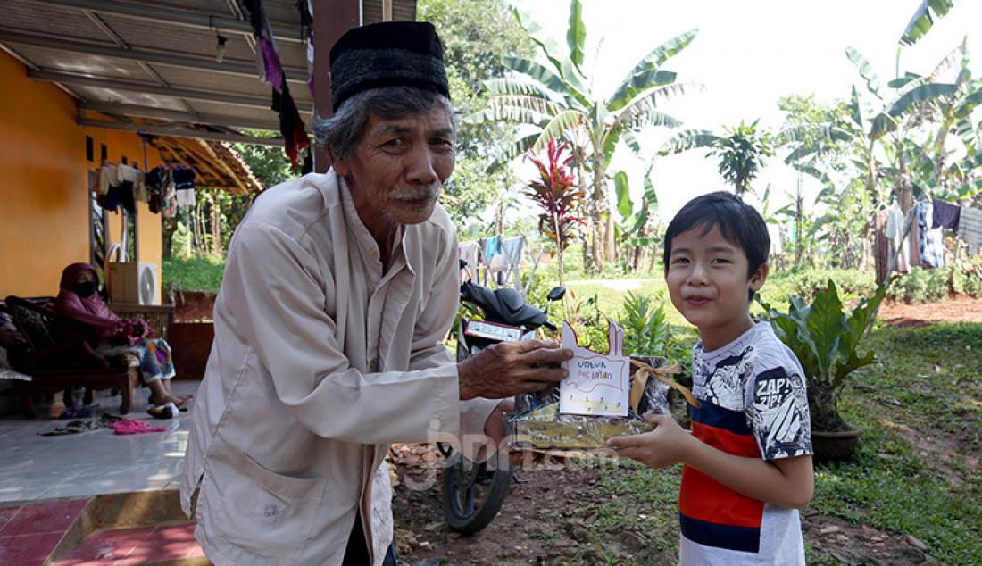 Anak TK membuat bingkisan parcel dari jajanannya dan memberikannya kepada seorang kakek yang sehari-hari bekerja sebagai petugas kebersihan, Tajur Halang, Kabupaten Bogor, Minggu (17/5). Foto: Ricardo - JPNN.com
