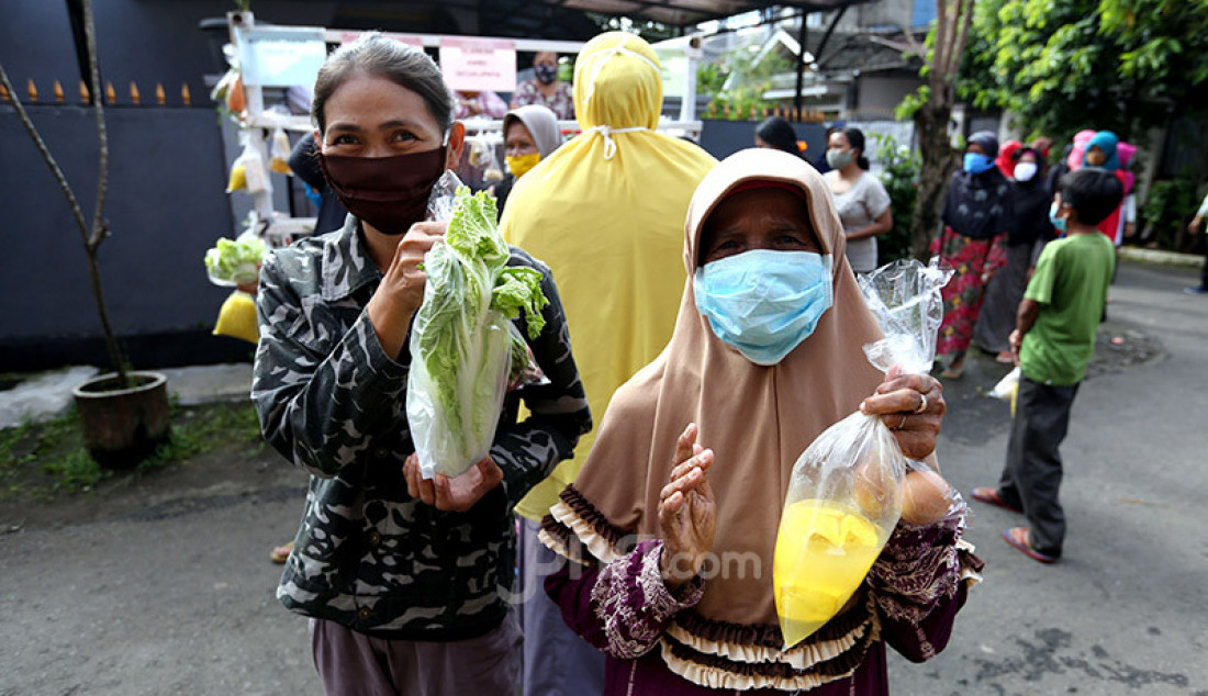 Warga terdampak Covid-19 antri mengambil bahan pangan gratis di Kompleks Bumi Menteng Asri, Menteng, Bogor, Kamis (21/5). Bahan pangan itu dikumpulkan warga setempat guna membantu yang tidak mampu selama Ramadhan. Foto: Ricardo - JPNN.com