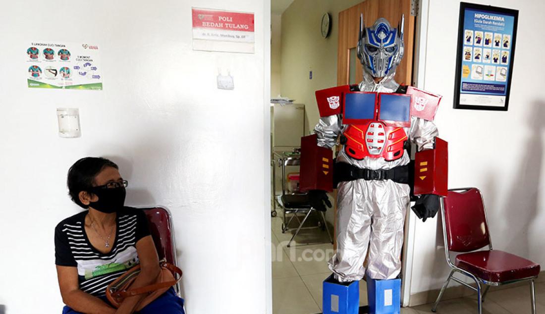 Dokter Rollando Erric Manibuy, SpOT mengenakan APD berkostum Transformer di RS Vania, Bogor, Jumat (22/5). Pemakian APD berkostum unik itu dilakukan agar pasien tetap terus optimis meghadapi Corona. Foto: Ricardo - JPNN.com