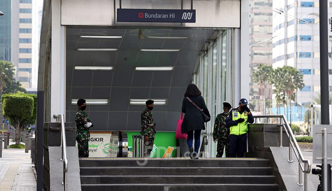 Anggota TNI berjaga di pintu masuk Halte Bus Transjakarta Bunderan HI, Jakarta, Rabu (27/5). Pemerintah akan segera menerapkan kebijakan di tempat keramaian yang akan kembali buka dan rencananya diterapkan minggu depan. Foto: Ricardo - JPNN.com