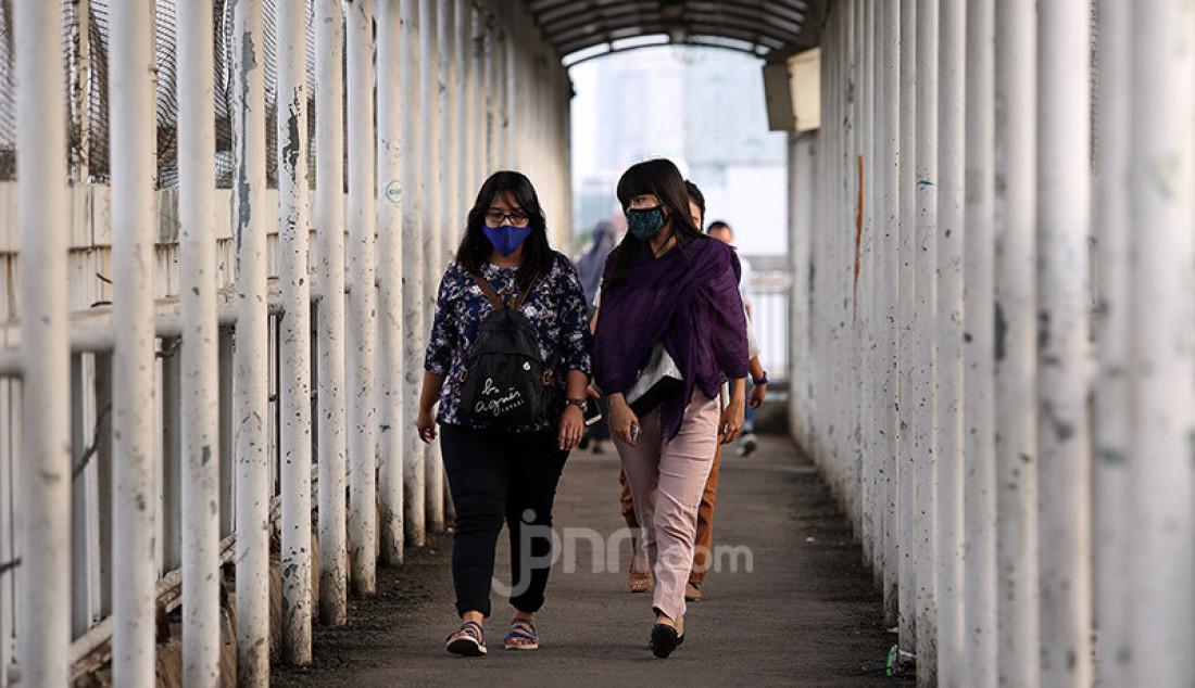 Warga saat berjalan di JPO jalan Gatot Subroto, Jakarta, Rabu (27/5). Pemerintah akan segera menerapkan kebijakan di tempat keramaian yang akan kembali buka (new normal) dan rencananya diterapkan minggu depan. Foto: Ricardo - JPNN.com