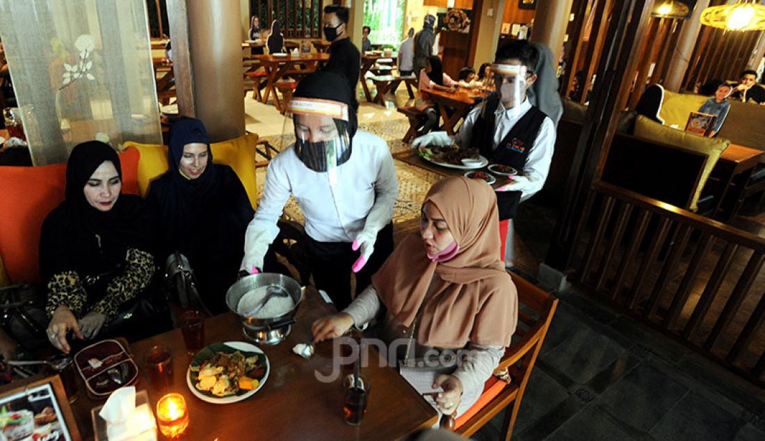 Pramusaji menggunakan alat pelindung diri wajah, masker dan sarung tangan di Rumah Makan Bumi Aki, Bogor, Senin (1/6). Penerapan protokol kesehatan ketat mulai dilakukan restoran dan rumah makan di Bogor. Foto: Ricardo - JPNN.com