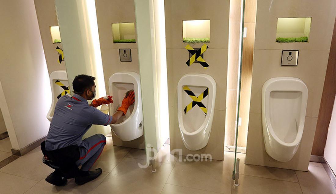 Petugas membersihkan urinoar atau peturasan di Lippo Mall Kemang, Jakarta, Selasa (2/6). Menjelang penerapan New Normal, Lippo Mall Kemang melakukan pembenahan dan penerapan protokol kesehatan. Foto: Ricardo - JPNN.com