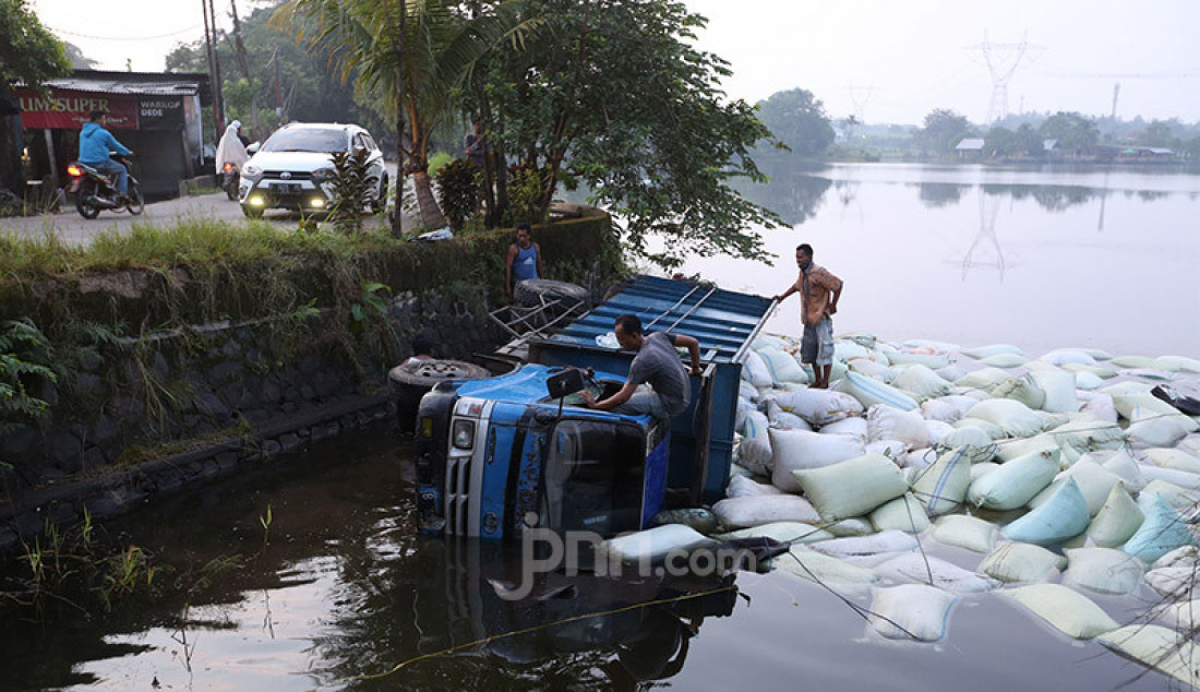 Sebuah truk pengangkut sekam masuk ke dalam Setu Tonjong, Tajur Halang, Kabupaten Bogor, Jawa Barat, Selasa (9/6). Kejadian tersebut pada waktu subuh dikarenakan pengemudi mengantuk. Foto: Ricardo - JPNN.com