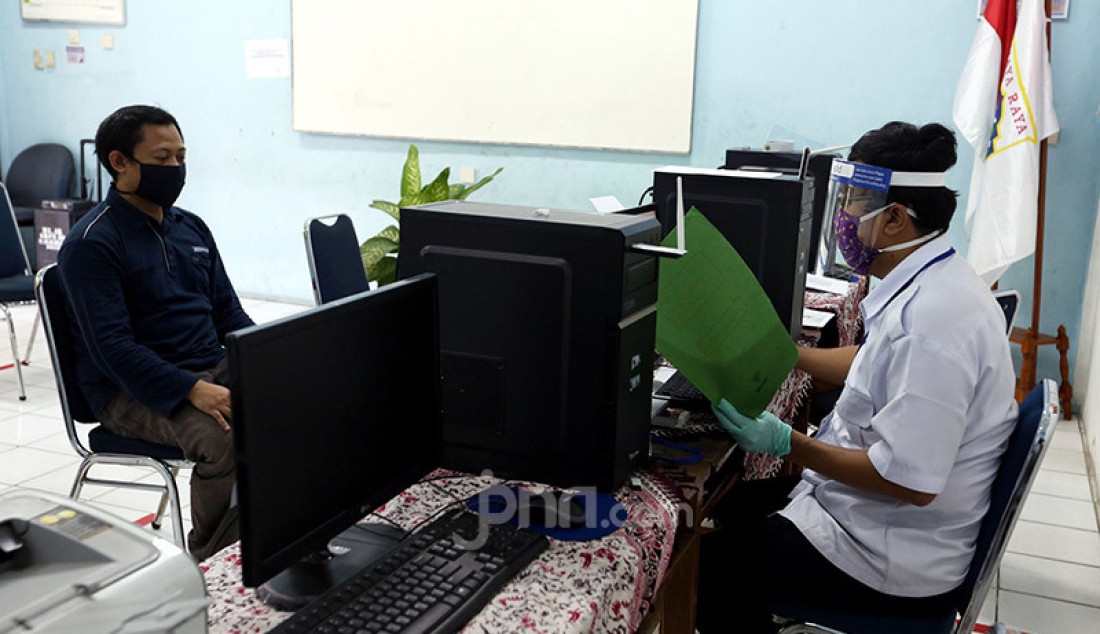 Petugas mengenakan masker dan pelindung wajah saat menerima wali murid di Posko Penerimaan Peserta Didik Baru (PPDB) SMP N 60, Jakarta, Selasa (16/6). Foto: Ricardo - JPNN.com