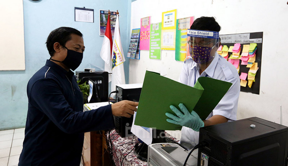 Petugas mengenakan masker dan pelindung wajah saat menerima wali murid di Posko Penerimaan Peserta Didik Baru (PPDB) SMP N 60, Jakarta, Selasa (16/6). Kemendikbud mengeluarkan panduan penyelenggaraan pembelajaran tahun ajaran dan tahun akademik baru. Foto: Ricardo - JPNN.com