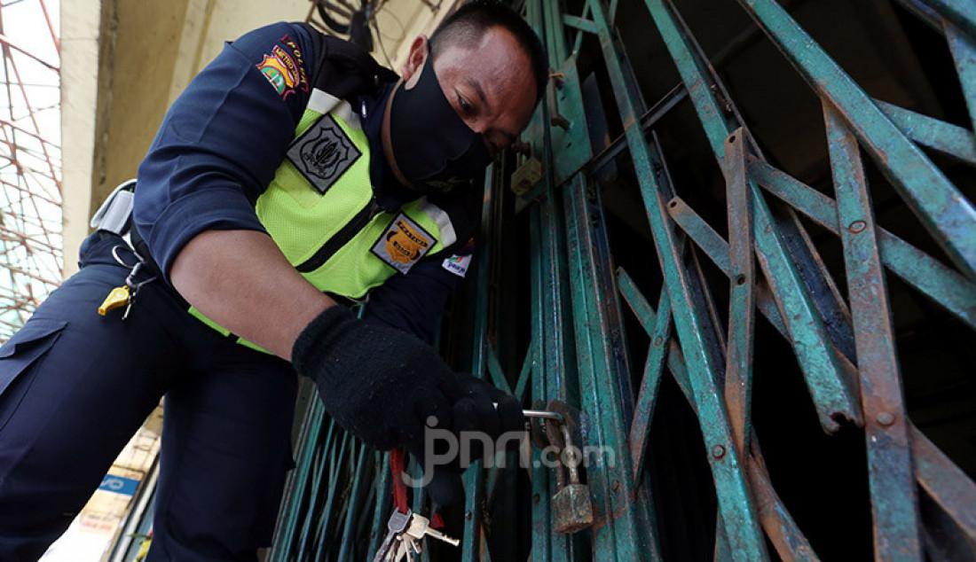 Petugas saat menutup akses masuk ke dalam Pasar Minggu, Jakarta, Sabtu (20/6). Pasar Minggu ditutup selama tiga hari mulai 20-23 Juni 2020 setelah 3 pedagang dinyatakan positif Covid-19. Foto: Ricardo - JPNN.com
