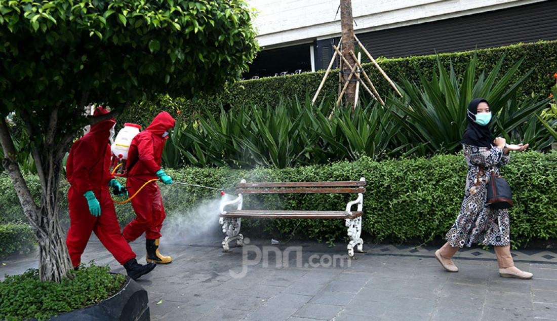 Petugas pemadam kebakaran menyemprotkan cairan disinfektan ke sejumlah fasilitas umum Jakarta, Sabtu (20/6). Penyemprotan cairan disinfektan tersebut dalam rangka persiapan jelang diadakannya kembali hari bebas kendaraan. Foto: Ricardo - JPNN.com