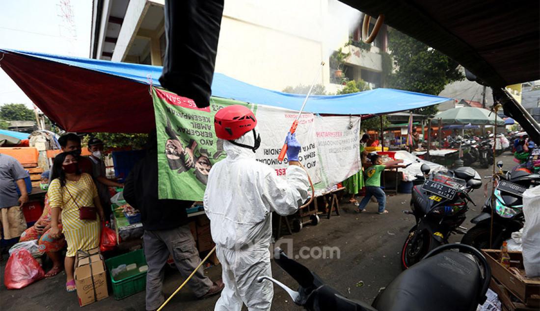 Petugas dari PMI menyemprotkan disinfektan di area Pasar Karang Anyar, Jakarta, Rabu (24/6). Penyemprotan tersebut untuk persiapan swab masal. Foto: Ricardo - JPNN.com