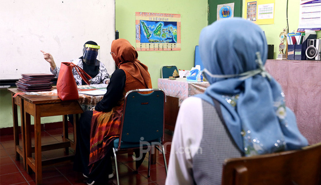 Orang tua murid saat mengambil hasil ujian usai menerima rapor kenaikan kelas kepada wali murid di SD Negeri Menteng 01, Jakarta, Kamis (25/6). Pembagian rapor dilaksanakan secara bertahap dari tanggal 24-26 Juni 2020, dengan mengikuti protokol kesehatan pencegahan penularan COVID-19. Foto: Ricardo - JPNN.com