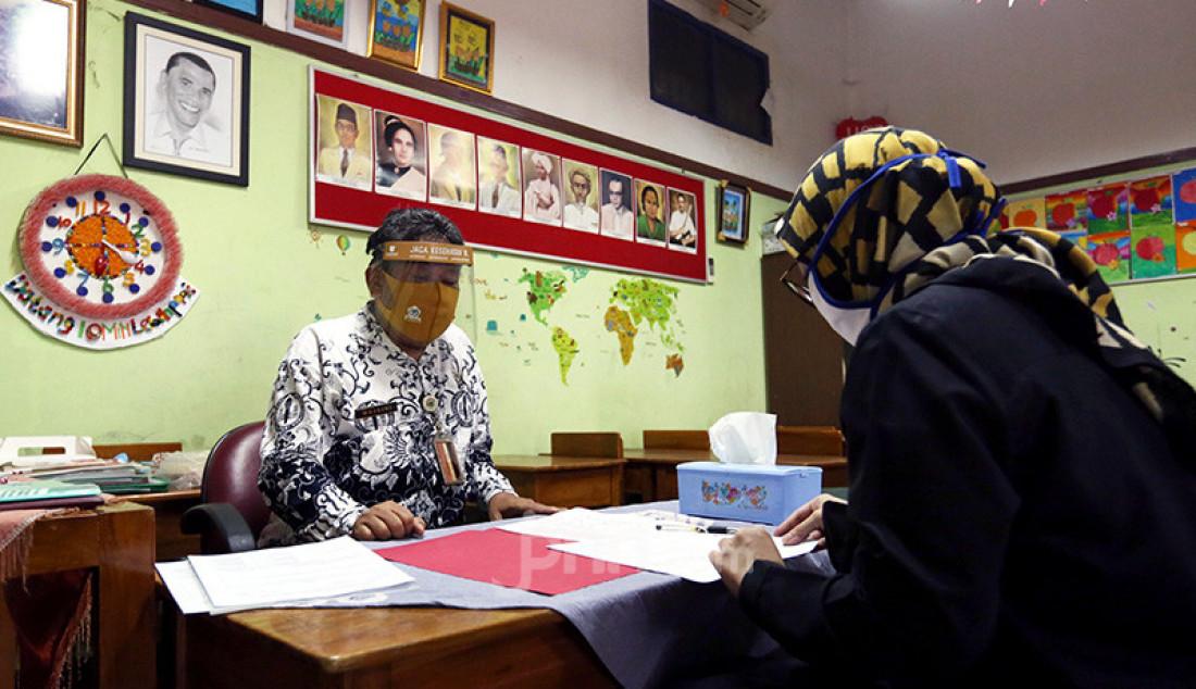 Guru membagikan laporan hasil belajar (rapor) kenaikan kelas kepada wali murid di SD Negeri Menteng 01, Jakarta, Kamis (25/6). Pembagian rapor dilaksanakan secara bertahap dari tanggal 24-26 Juni 2020, dengan mengikuti protokol kesehatan pencegahan penularan COVID-19. Foto: Ricardo - JPNN.com