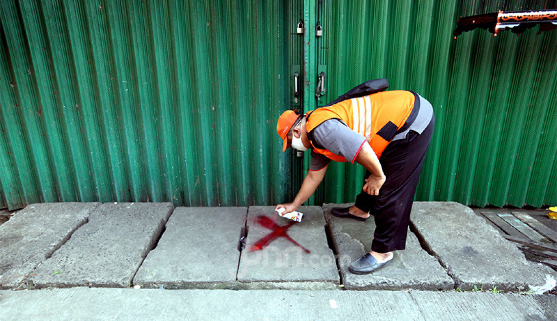 Petugas memberikan tanda silang di depan lapak pedagang Pasar Karang Anyar, Jakarta, Kamis (25/6). Pemberian tanda tersebut untuk pedagang yang tidak mau mengikuti tes swab Covid 19. Foto: Ricardo - JPNN.com