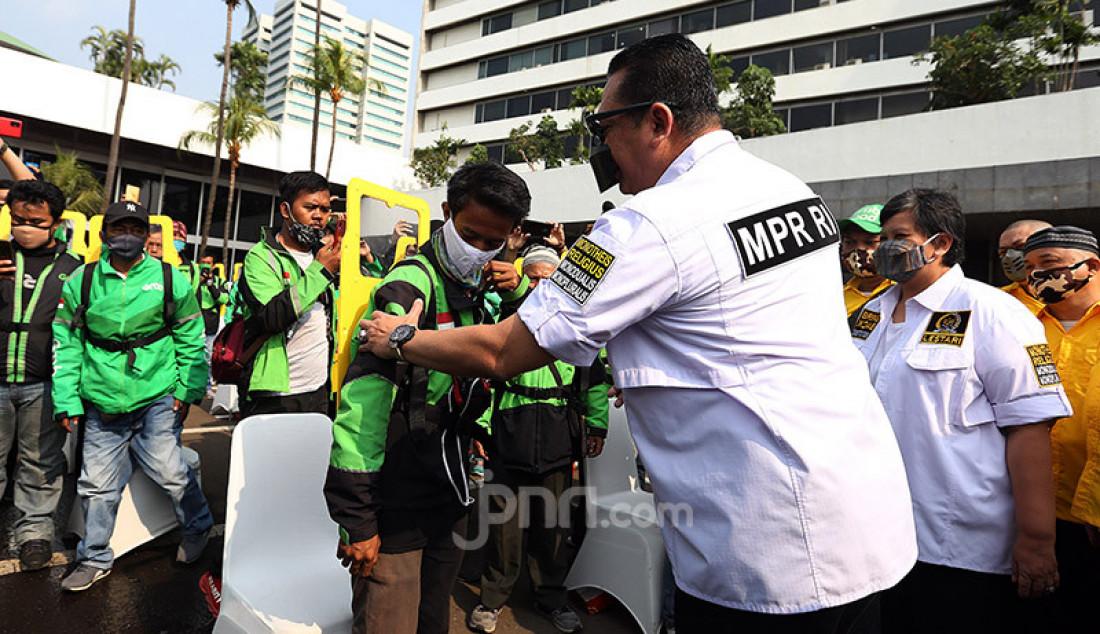 Ketua MPR Bambang Soesatyo bersama pimpinan MPR Ahmad Basarah dan Lestari Moerdijat memberikan bantuan partisi/sekat pemisah kepada 200 pengemudi ojek online di Lobi Gedung Nusantara III MPR/DPR/DPD, Jakarta, Sabtu (27/6). Foto: Ricardo - JPNN.com
