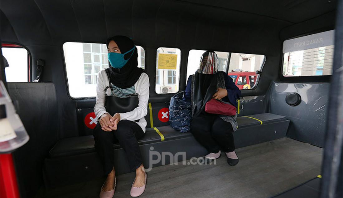 Seorang penumpang saat menaiki angkot di Terminal Pinang Ranti, Jakarta, Jumat (3/7). Dinas Perhubungan DKI Jakarta mengoperasikan kembali layanan angkot mikrotrans yang terintegrasi dalam program Jak Lingko dengan menerapkan protokol kesehatan. Foto: Ricardo - JPNN.com