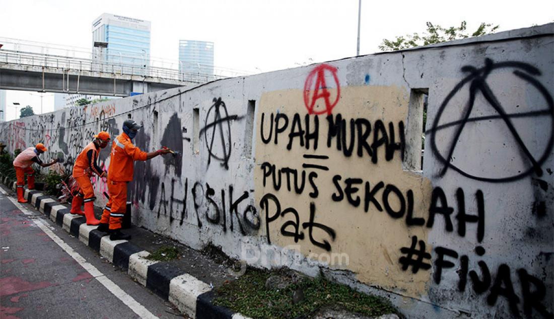 Petugas PPSU membersihkan tulisan vandalisme pasca aksi demo menolak RUU HIP dan RUU Omnibus Law Cipta Kerja di depan Gedung DPR/MPR/DPD, Jakarta, Jumat (17/7). Foto: Ricardo - JPNN.com