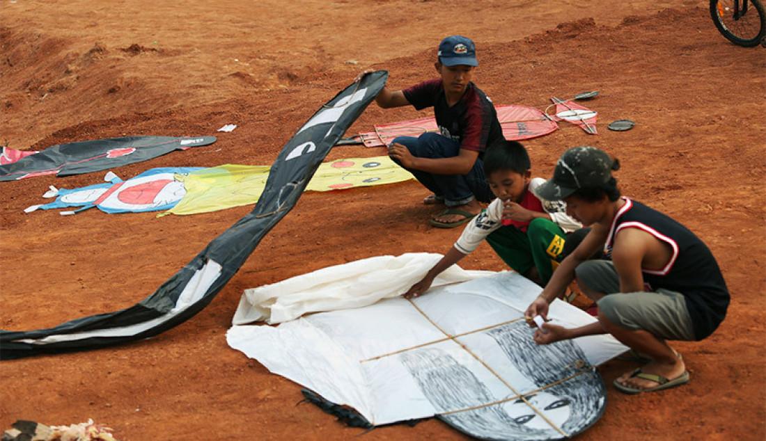 Anak-anak mempersiapkan layang-layang untuk diterbangkan di tanah lapang kawasan Sawangan, Depok, Jawa Barat, Sabtu (25/7). Bermain layang-layang menjadi alternatif hiburan tersendiri bagi anak-anak ditengah masa pandemi Covid-19 yang belum juga berakhir. Foto: Ricardo - JPNN.com