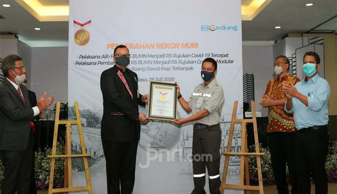 Senior Manager MURI Awan Rahargo (kiri) memberikan penghargaan kepada kepada Manajer Divisi Konstruksi 1 Kurniawan Prabawayudha di Jakarta, Selasa (28/7). WEGE memperoleh penghargaan dari Museum Rekor Dunia Indonesia (MURI) sebagai Pelaksana/kontraktor dua proyek Rumah Sakit Rujukan Covid 19 milik Pertamina. Rekor pertama sebagai Pelaksana Alih Fungsi RS BUMN menjadi RS Rujukan Covid-19 Tercepat (RS Pertamina Jaya Jakarta) dan yang kedua, Pelaksana Pembangunan RS BUMN Rujukan Covid - 19 Modular dengan Ruang Rawat Inap Terbanyak (RSPP Extension COVID-19 Simprug Jakarta). Foto: Ricardo - JPNN.com