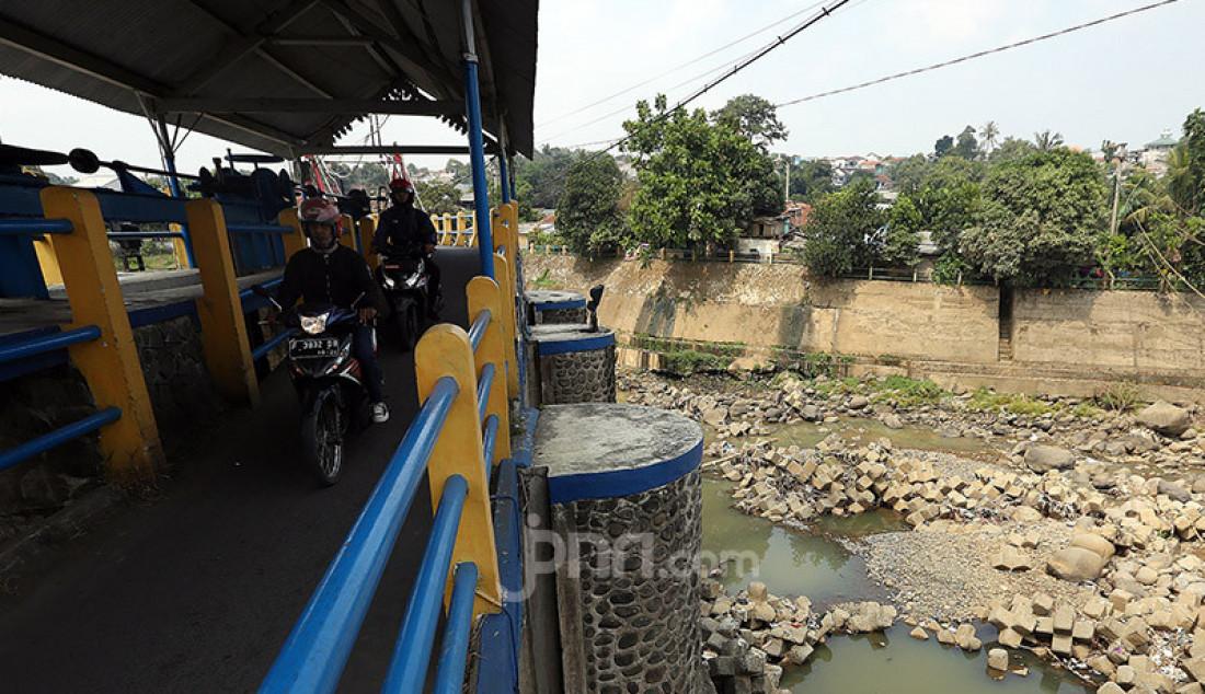 Warga meilntas di atas Bendungan Katulampa, Kota Bogor, Senin (3/8). Debit air sungai Ciliwung di Bendung Katulampa, Bogor terus mengalami penyusutan sejak satu bulan terakhir di awal musim kemarau dengan kondisi aliran air hanya 100 liter per detik dan ketinggian air 0 cm. Foto: Ricardo - JPNN.com