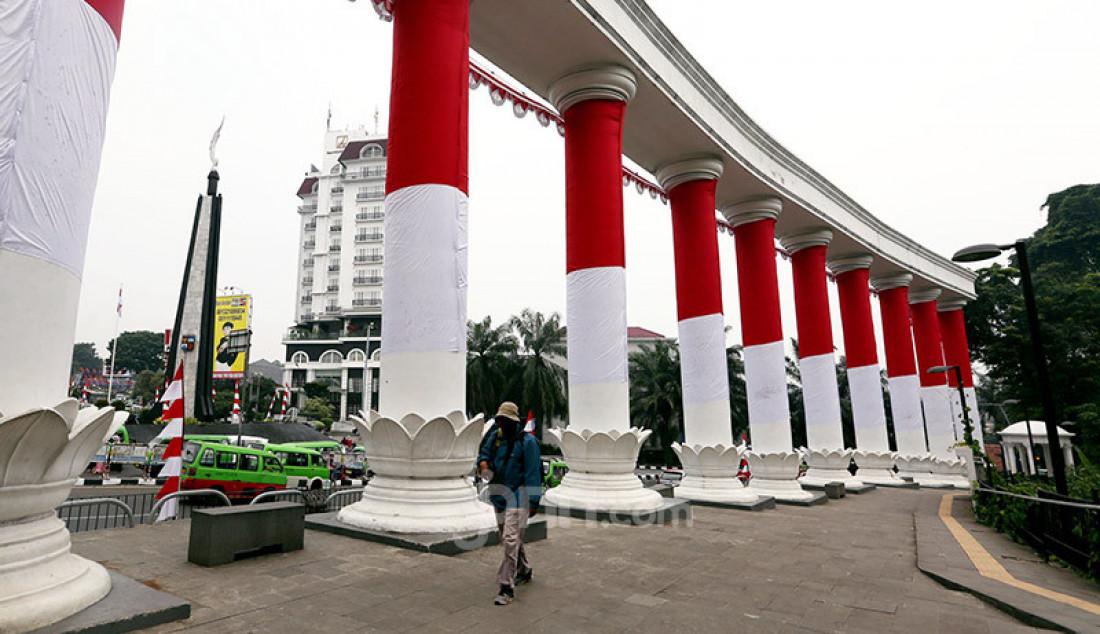 Warga melintas di Tepas Lawang Salapan yang dibalut dengan bendera merah putih di jalan Otto Iskandardinata, Kota Bogor, Selasa (4/8). Pemasangan bendera merah putih pada sepuluh tiang pilar ikon baru Kota Bogor tersebut merupakan rangkaian kegiatan Festival Merah Putih 2020 sekaligus menyambut HUT ke-75 Kemerdekaan RI. Foto: Ricardo - JPNN.com