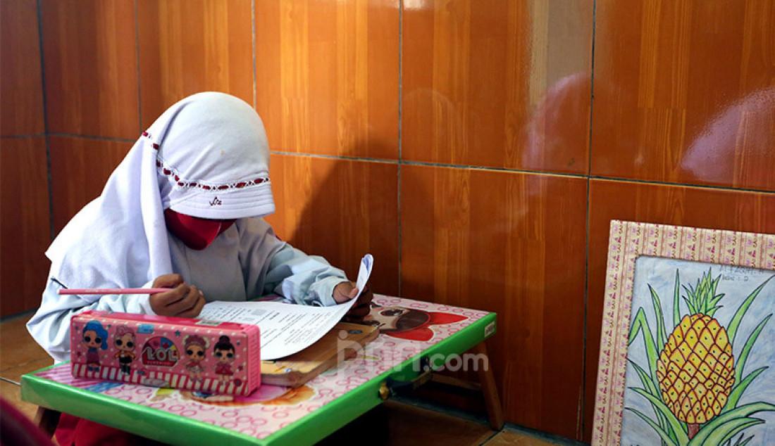 Siswa kelas 2 belajar di Majelis Taklim Bani Umar, Kampung Bubulak, Kota Bogor, Selasa (11/8). Guru membantu siswa untuk belajar dan mengerjakan evaluasi secara tatap muka karena orang tua mengalami kesulitan membantu anak dalam belajar secara daring. Foto: Ricardo - JPNN.com
