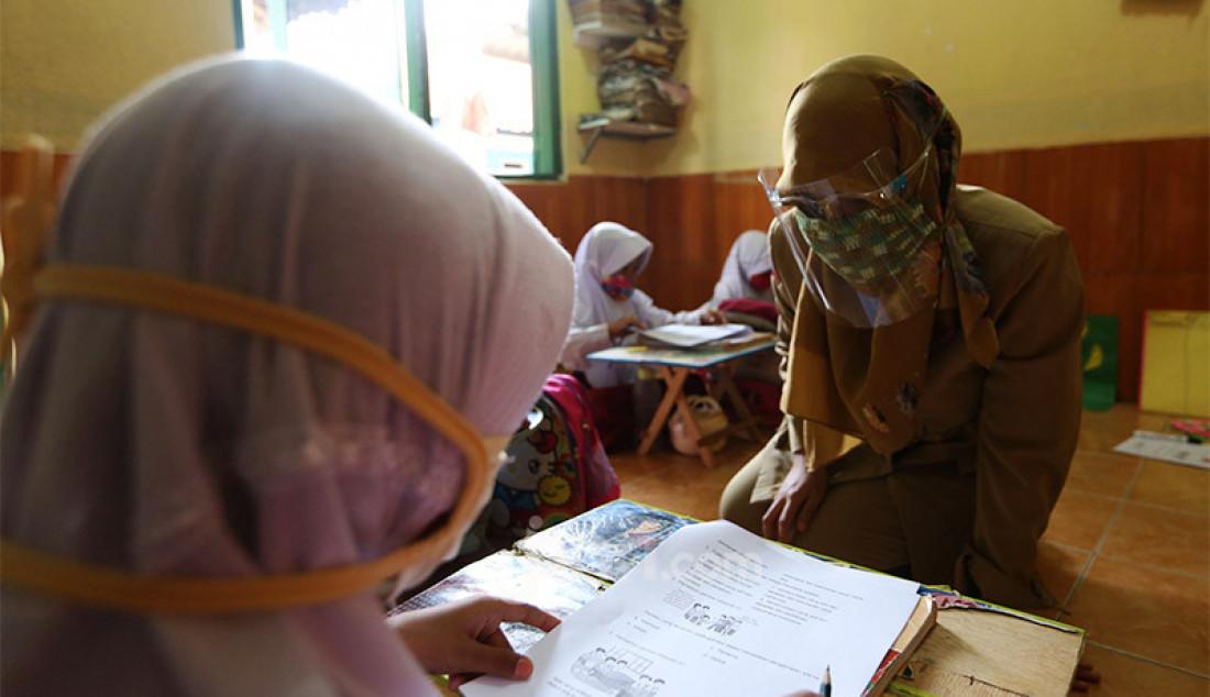 Guru SDN Bubulak 02 mengajarkan siswa kelas 2 di Majelis Taklim Bani Umar, Kampung Bubulak, Kota Bogor, Selasa (11/8). Guru membantu siswa untuk belajar dan mengerjakan evaluasi secara tatap muka karena orang tua mengalami kesulitan membantu anak dalam belajar secara daring. Foto: Ricardo - JPNN.com