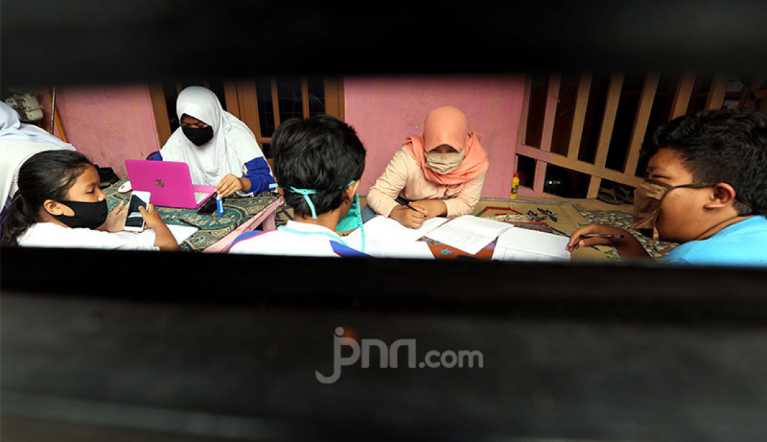 Sejumlah siswa mengerjakan tugas sekolah secara daring di Gang Kelor, Menteng, Bogor, Kamis (13/8). Warga RW 10 di lingkungan tersebut menggalang Gerakan Berbagi Internet atau Wifi dengan menyetorkan minyak jelantah, sampah anorganik dan bibit pohon kelor sebagai upaya membantu siswa dalam pembelajaran daring yang terkendala kuota dan jaringan internet. Foto: Ricardo - JPNN.com