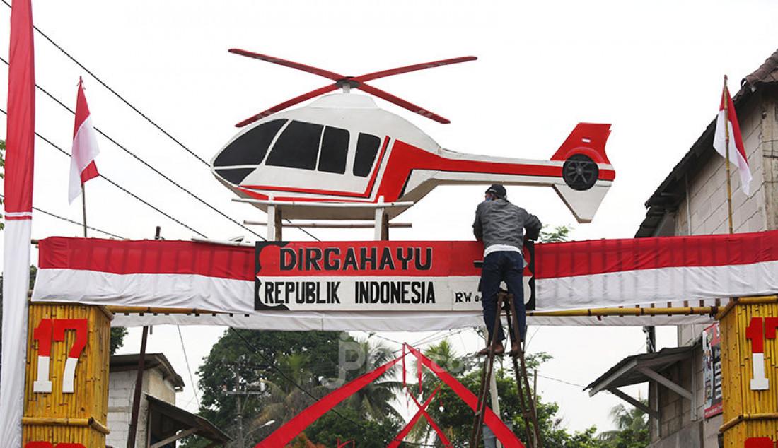 Warga saat menbuat gapura dengan hiasan helikopter di Desa Cihideung Udik, Ciampea, Kabupaten Bogor, Jumat (14/8). Untuk menyambut HUT ke-75 Kemerdekaan RI, sejumlah warga menghiasi daerahnya masing-masing. Foto: Ricardo - JPNN.com