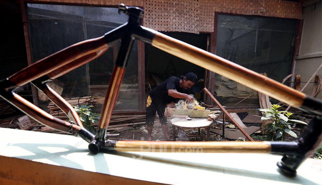 Pengrajin menyelesaikan pembuatan frame sepeda kayu di Jalan Nangka Raya No.750, Tapos, Depok, Sabtu (15/8). Sepeda kayu yang diproduksi oleh Kayuh Indonesia dan dikelola Didi Diarsa Adiana memiliki inovasi dan keunikan. Bergerak hampir sudah 4 tahun, omsetnya kini mencapai Rp 30 juta per bulan dengan pemasaran melalui media sosial. Foto: Ricardo - JPNN.com